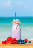 Fresh blended berries in a shake against beach background.