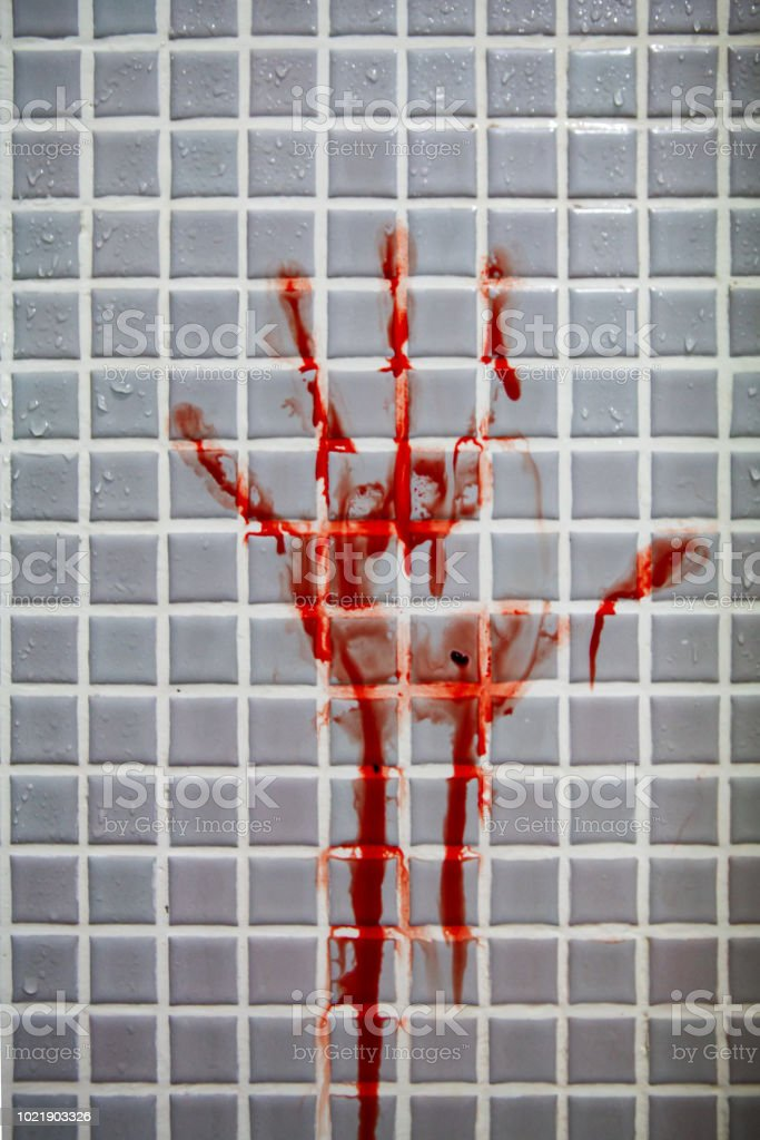 Fresh bloody handprint or bloodstains with streaks on wet bathroom tiles wall. stock photo