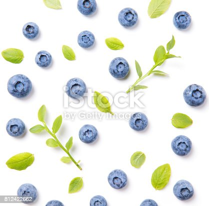 670420880istockphoto Fresh blueberries and leaves, berry ornament pattern on white background, closeup, top view 812422662