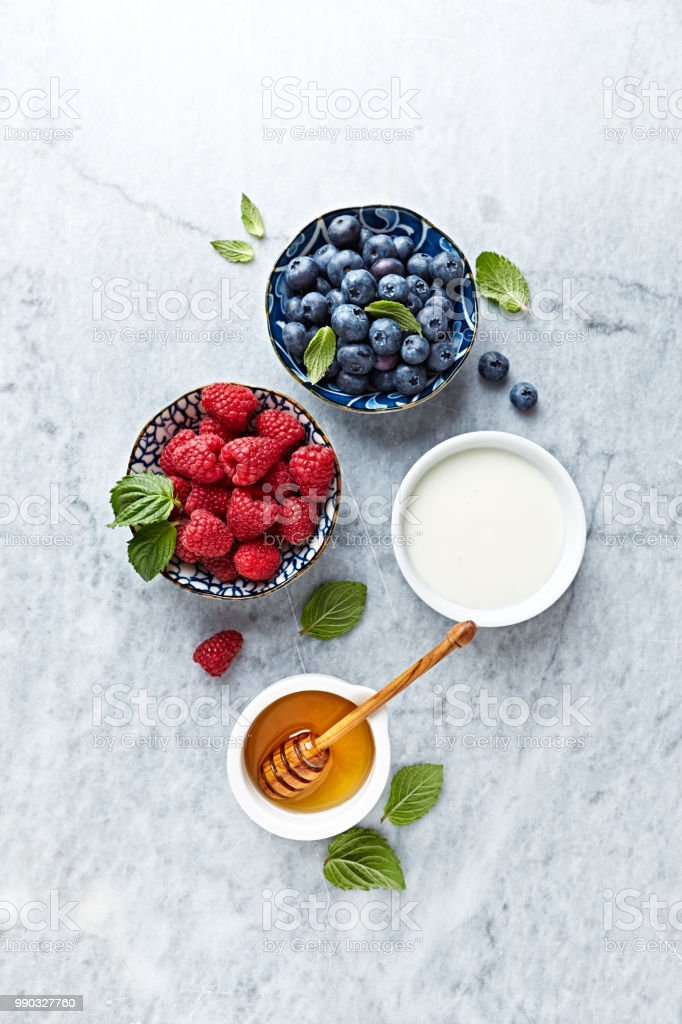 Fresh Blueberries and Raspberries with Honey, Jogurt and Mint Leaves on gray marble background. Flat lay. Healthy Diet Concept. stock photo