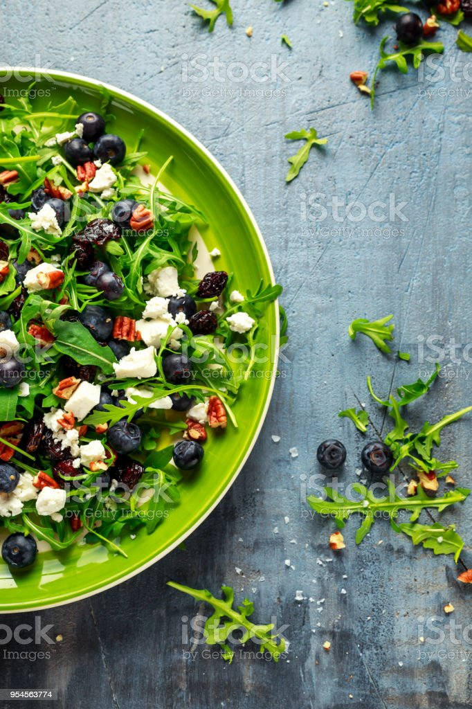 Fresh Blueberries, Cranberry salad with arugula, nuts, feta cheese, olive oil, herbs. Morning, breakfast healthy food stock photo