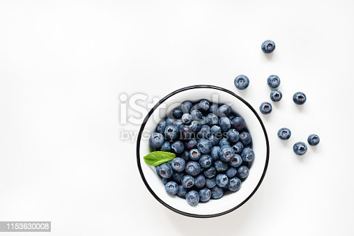 Fresh blueberries in bowl on white background. Berries isolated. Table top view. Healthy vegetarian and vegan product, trendy superfood