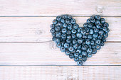 Fresh blueberries in the shape of a heart on rustic wooden cozy background