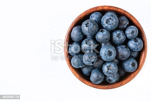 670420880istockphoto Fresh blueberries in wooden bowl on white background 955998728