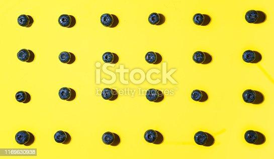 670420880istockphoto Fresh blueberry pattern on yellow background. 1169630938