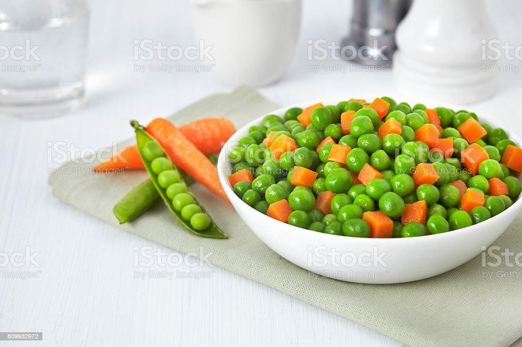 Fresh bowl of green beans and cubed carrots on white stock photo