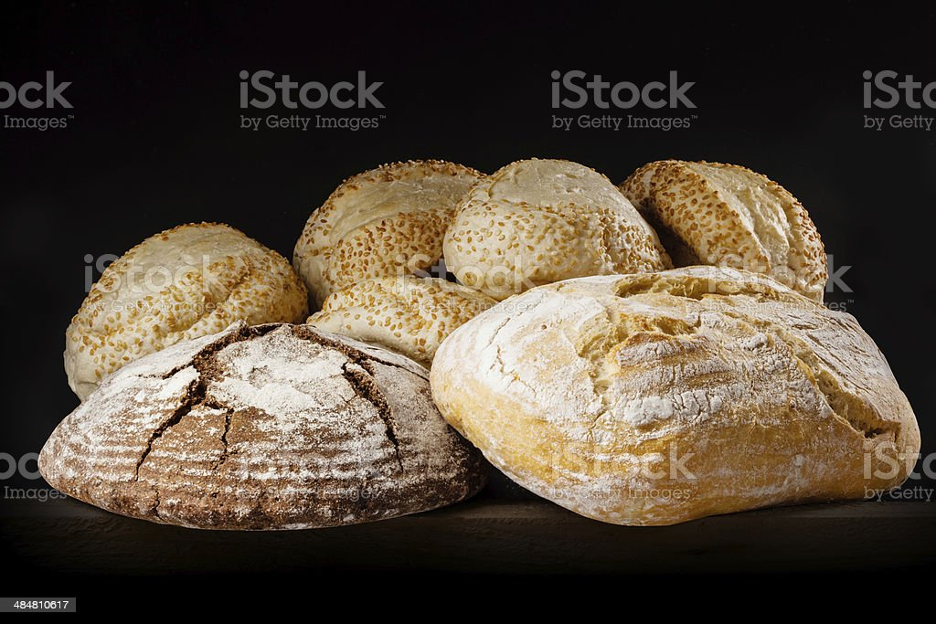 Fresh bread and buns with sesame on dark background. stock photo