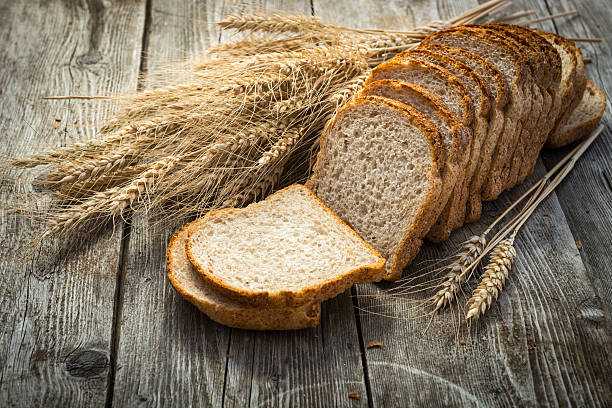 fresh bread  and wheat on the wooden loaf of bread and rye on the wooden background whole wheat stock pictures, royalty-free photos & images