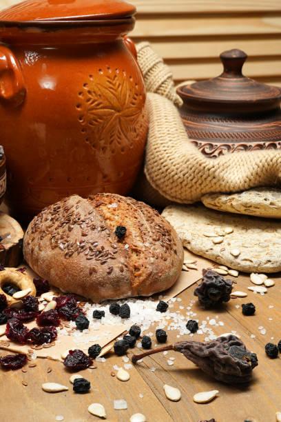 pan fresco, bagels, frutos secos, semillas, sal, tarro y trigo en la madera - bodegón y concepto de alimentación saludable - foto de stock