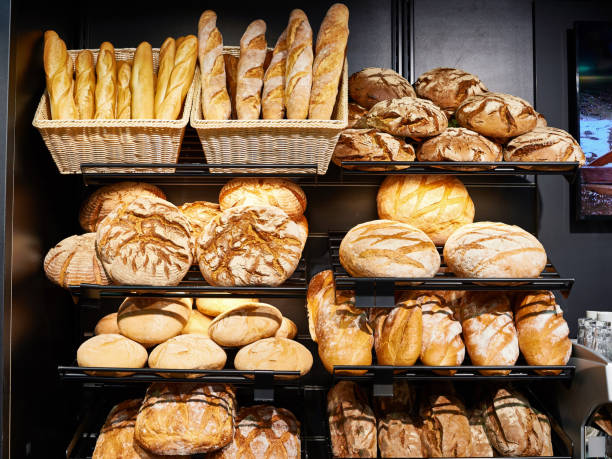fresh bread on shelves in bakery - panetteria foto e immagini stock