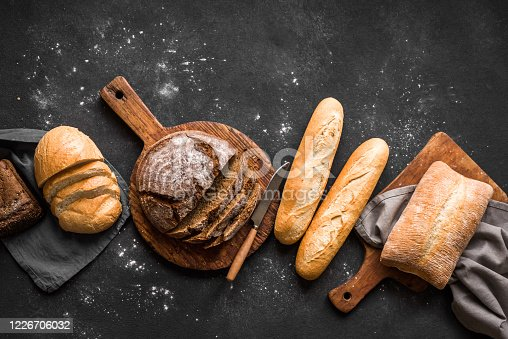 Fresh Bread on black background, top view, copy space. Homemade fresh baked various loafs of wheat and rye bread flat lay.