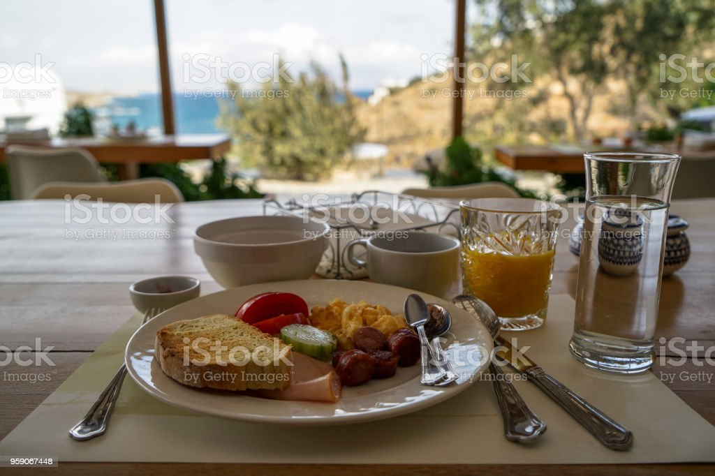 Fresh breakfast plate on wooden table including omelette, sausage, ham, tomato, cucumber, bread, orange juice, coffee and water with beautiful blurred seaview background, Mykonos stock photo