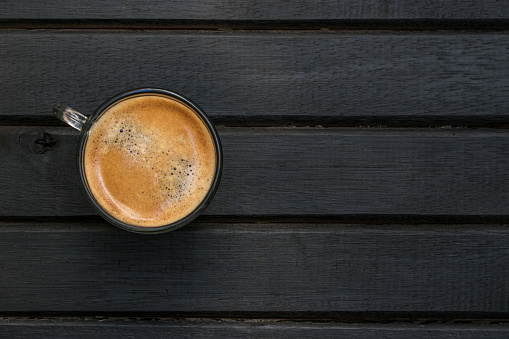 Fresh brewed espresso coffee on a black wood table, with wood grain, lines, pattern and texture, and copy space to the right
