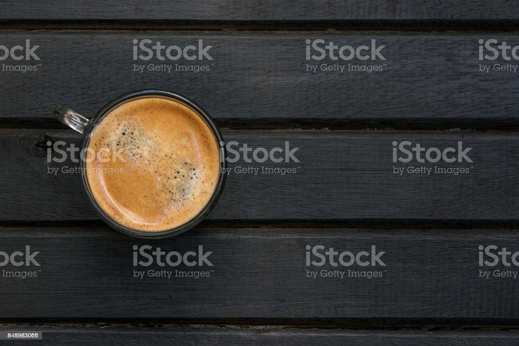 Café expresso café fresco sobre uma mesa de madeira preta, com grão de madeira, linhas, padrão e textura e cópia espaço à direita - foto de acervo