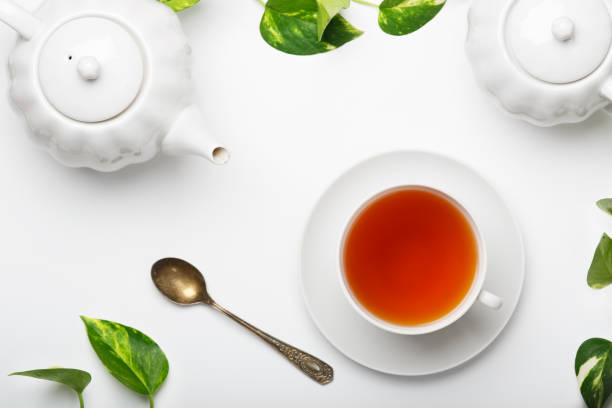 Fresh brewed tea, teapot, sugar bowl on a light table. White dishes. White background. Top view. stock photo