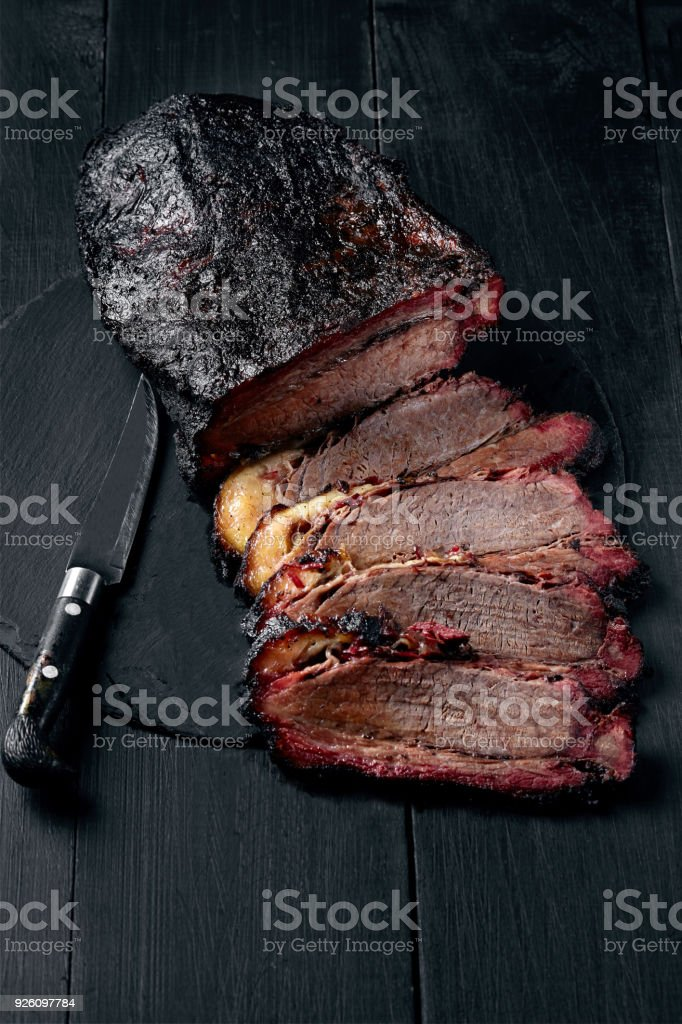 Fresh Brisket BBQ beef sliced for serving against a dark background stock photo