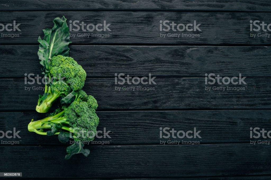 Brócolis fresco em um fundo preto de madeira. Vista superior. Copie o espaço. Brócolis fresco em um fundo preto de madeira. Vista superior. Copie o espaço. - Foto de stock de Agricultura royalty-free