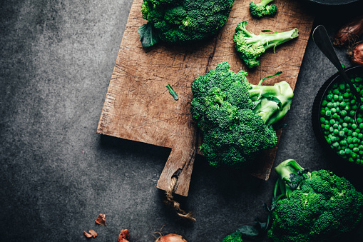 Directly above shot of fresh broccoli on chopping board with green peas bowl. Ingredients for making green vegan soup in kitchen.