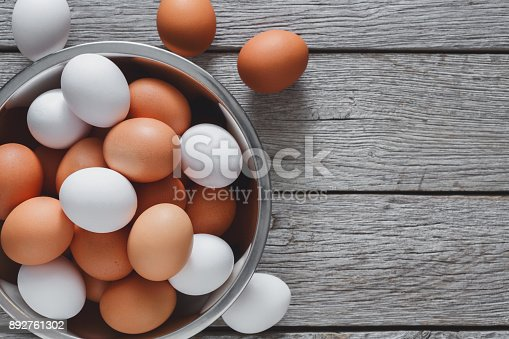istock Fresh brown eggs in bowl on wood background 892761302