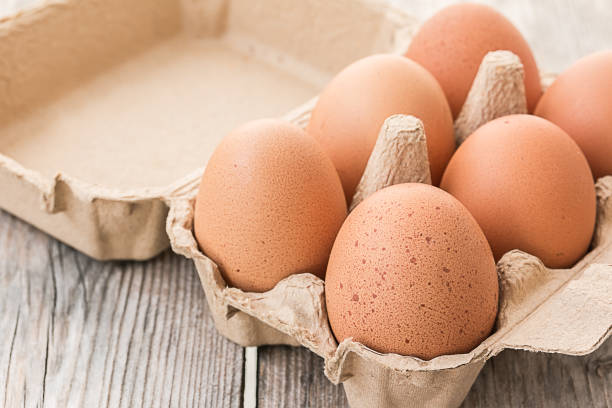 verse bruine eieren in karton op houten tafel - chicken bird in box stockfoto's en -beelden