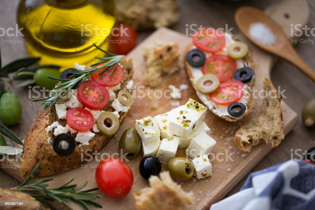 Fresh bruschetta on wooden cutting board with vegetables royalty-free stock photo