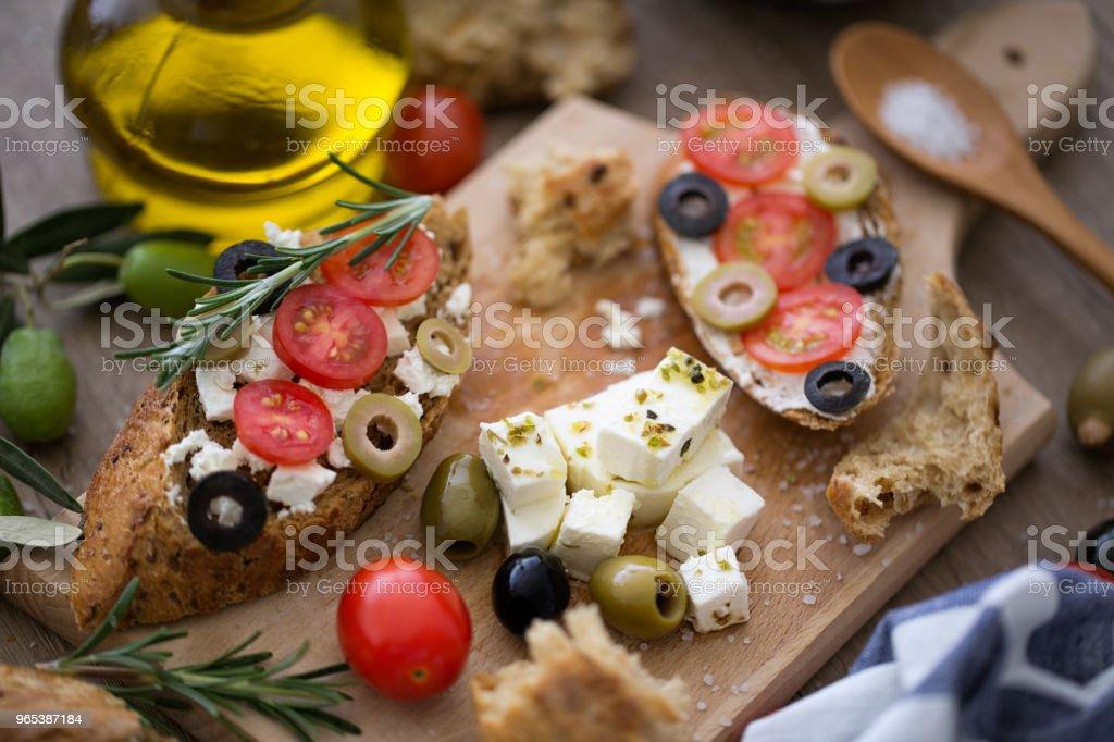 Bruschetta fraîche sur une planche à découper en bois avec légumes - Photo de Aliment libre de droits
