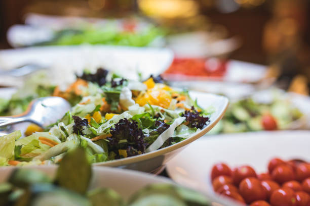 A fresh buffet of healthy salads A fresh buffet of a colorful variety of healthy organic salads. Focus is on a salad bowl of mixed leafs and carrots, and there is a bowl of tomatoes on the right side. buffet stock pictures, royalty-free photos & images