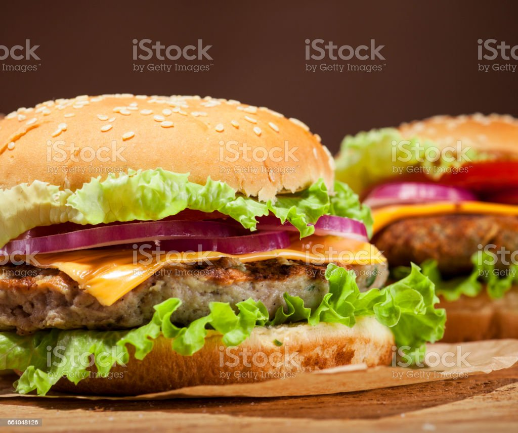 Fresh burgers on wooden background Fresh delicious burgers with meatball, cheese, tomato, onion and lettuce on wooden table and dark background with copy space American Culture Stock Photo