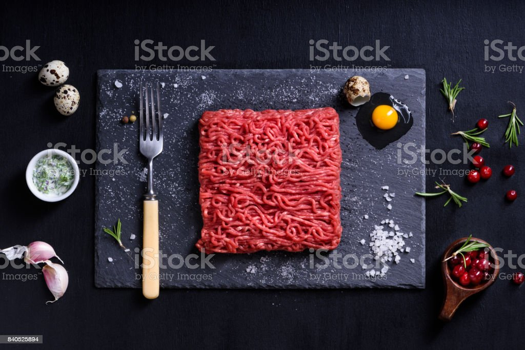 Fresh butcher cut meat minced, garnished, served with cooking ingredients. stock photo