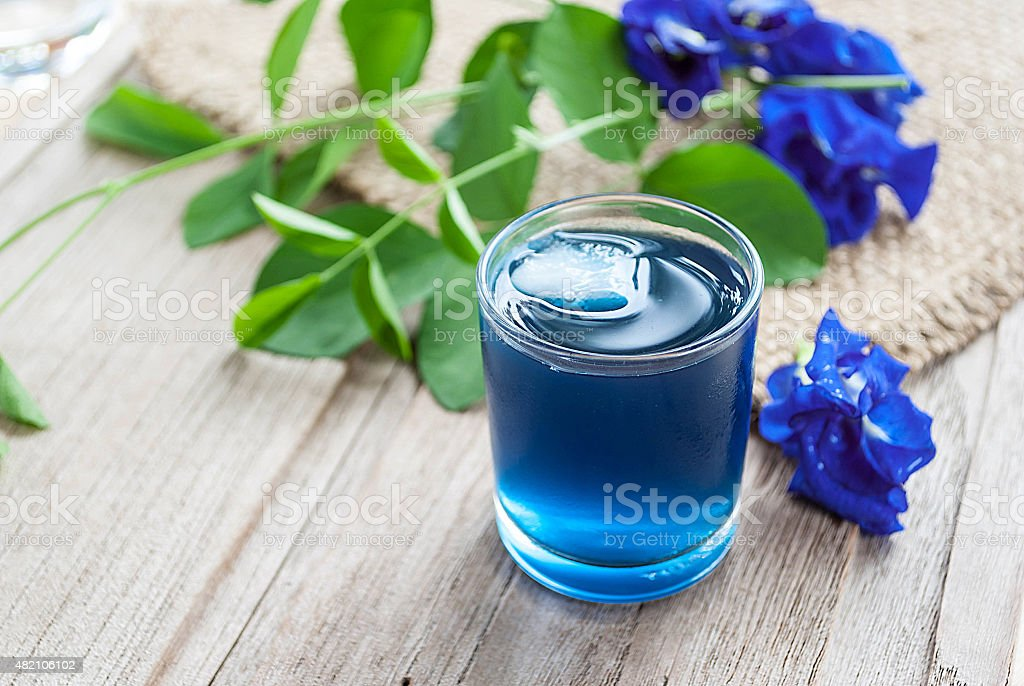 Fresh butterfly pea juice and butterfly pea flower on wooden stock photo