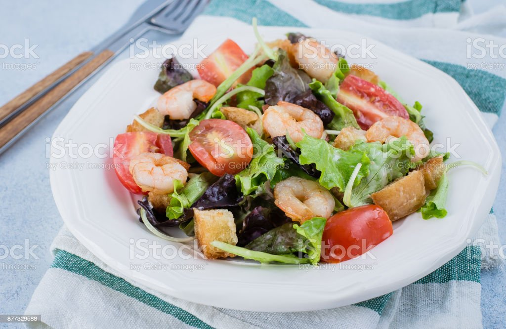 Fresh caesar salad on white plate with lettuce, cherry, parmesan cheese and shrimps on stone table background. Healhty Food Snack Concept. Top view Copy Space stock photo