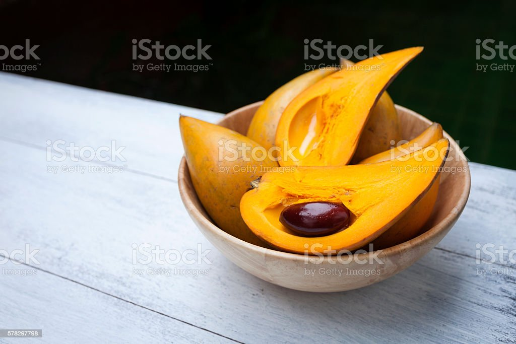 Fresh Canistel fruit in wooden bowl stock photo