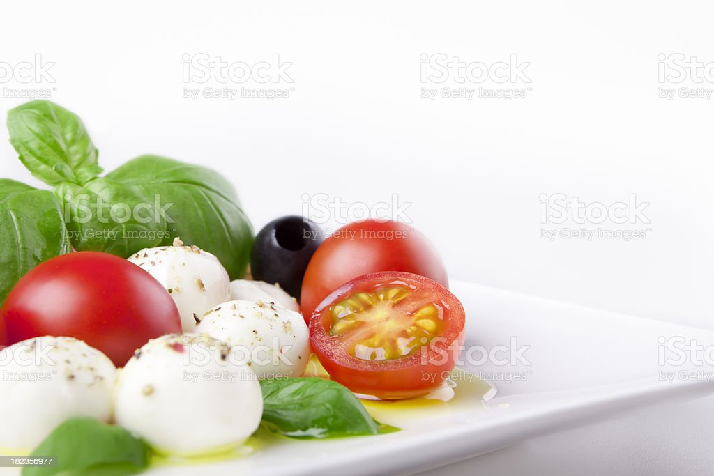 Fresh Caprese salad on a table in bright light royalty-free stock photo