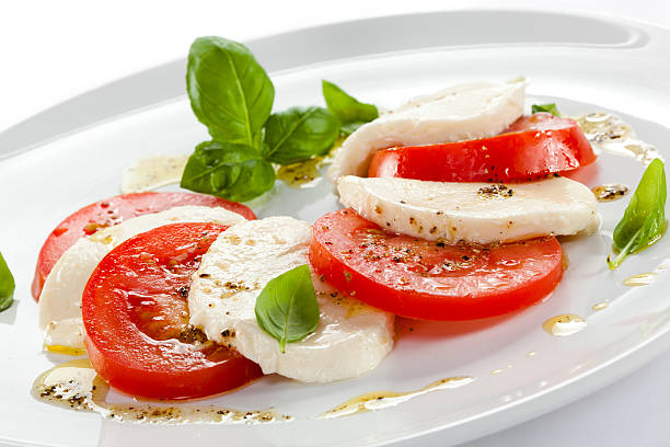 Fresh caprese salad with basil leaves on white plate
