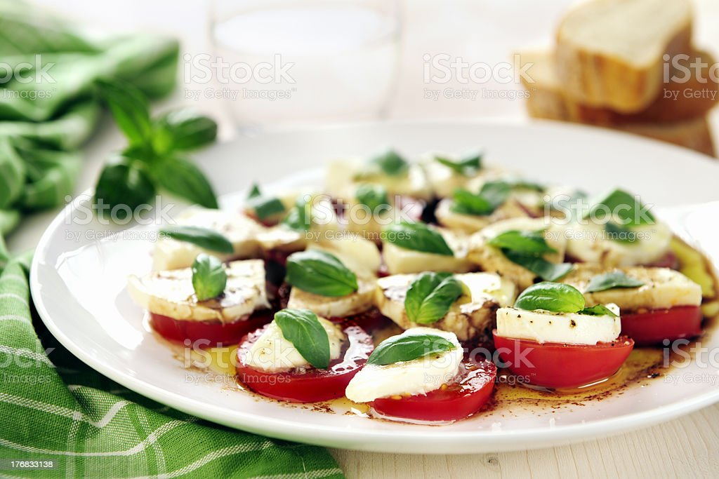 Fresh caprese salad with delicious tomatoes + mozzarella and bas royalty-free stock photo