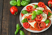Fresh caprese salad with mozzarella, tomato, basil and spices on the plate