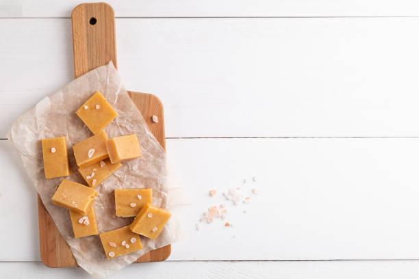 verse karamel fudge snoepjes op witte rustieke achtergrond - fudge stockfoto's en -beelden