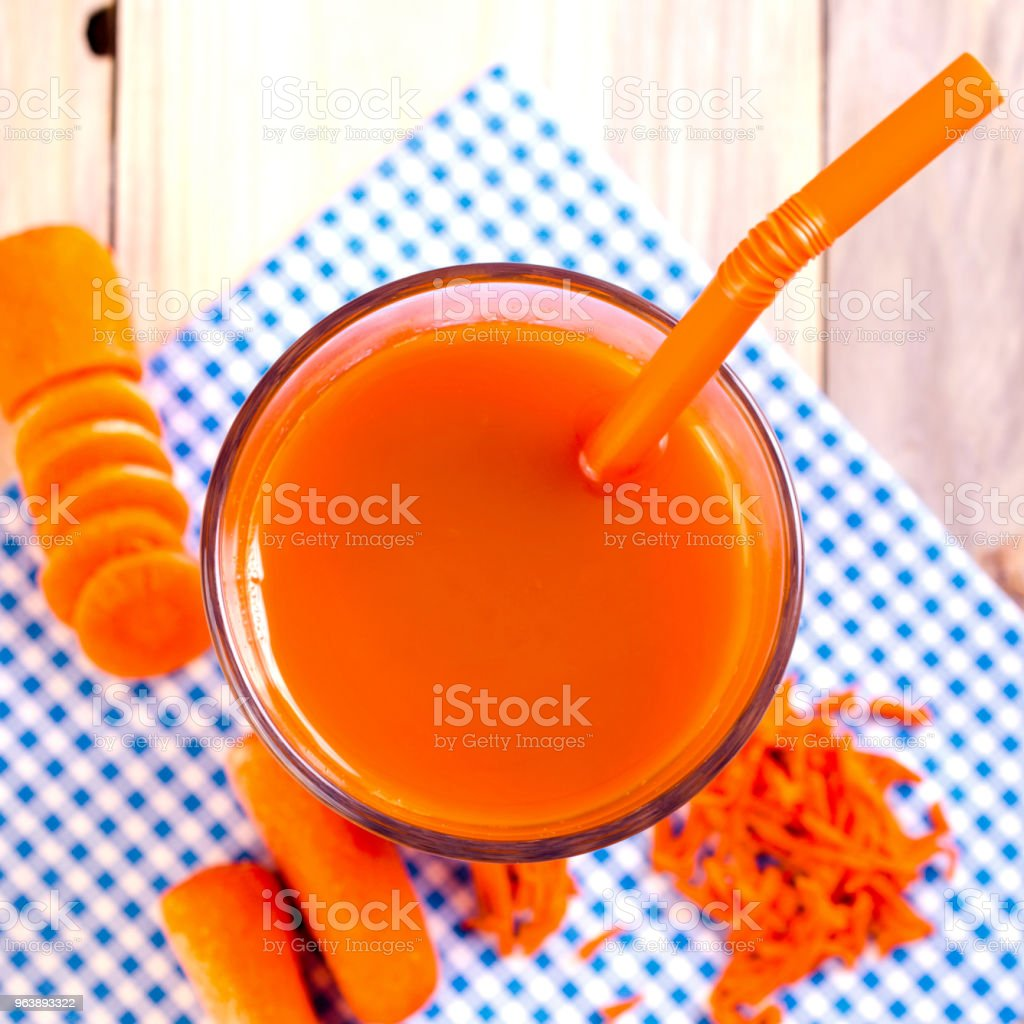 Fresh carrot juice in transparent glass with cocktail tubule on a blue napkin. Concept healthy beverage. Top view. Square. - Royalty-free Backgrounds Stock Photo