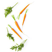 Fresh carrots and carrot stalks on white background; flat lay; organic veggetables; copy space; white background