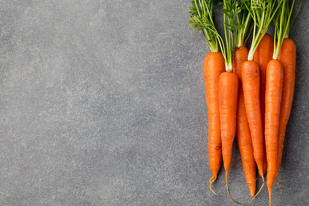fresh carrots bunch on a grey stone background copy space - carrots stock photos and pictures