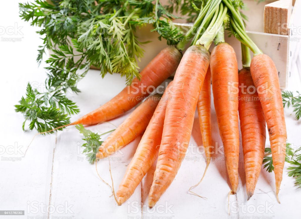 close up of fresh carrots on wooden table