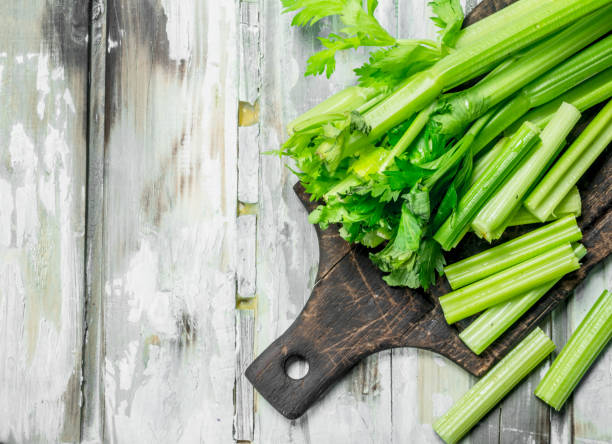 Fresh celery on a cutting Board. Fresh celery on a cutting Board. On wooden background celery stock pictures, royalty-free photos & images