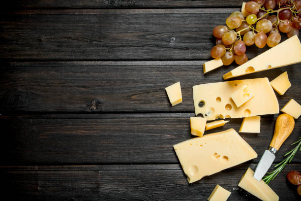 fresh cheese with grapes. - maasdam foto e immagini stock