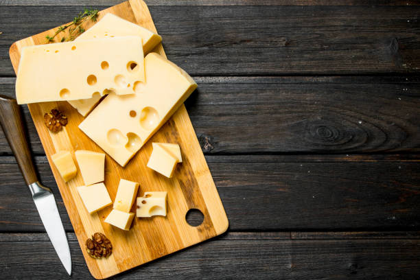 fresh cheese with nuts on a wooden board. - maasdam foto e immagini stock