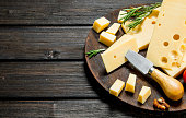 Fresh cheese with rosemary on the cutting Board. On a wooden background.
