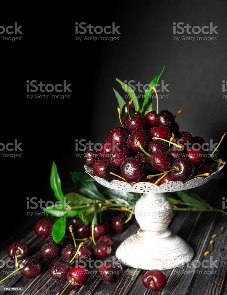 Fresh cherries in a decorative stand, on a dark wooden background with copy space. The concept of summer and harvest. Cherry Macro. Vegan, vegetarian, raw food royalty-free stock photo