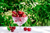 Fresh cherries in crystal bowl on a table with a white cloth on a green natural background of blurred flowers. Concept of healthy food, vitamin C. Copy space for your text.