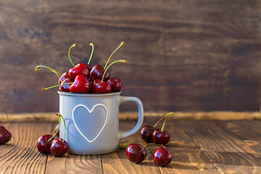 Fresh cherries in grey heart shaped cup on wooden table