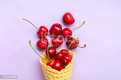 Fresh cherries in waffle cones Ice cream cone filled with fresh sweet cherry on lilac background. Top view. Copy space. Summer creative concept Flat lay Healthy food.