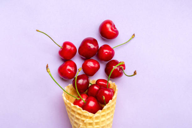 Fresh cherries in waffle cones Ice cream cone filled with fresh sweet cherry on lilac background. Top view. Copy space. Summer creative concept Flat lay Healthy food Fresh cherries in waffle cones Ice cream cone filled with fresh sweet cherry on lilac background. Top view. Copy space. Summer creative concept Flat lay Healthy food. muziekfestival stock pictures, royalty-free photos & images
